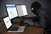 Hacker Wearing Balaclava Hacking Computers At Desk